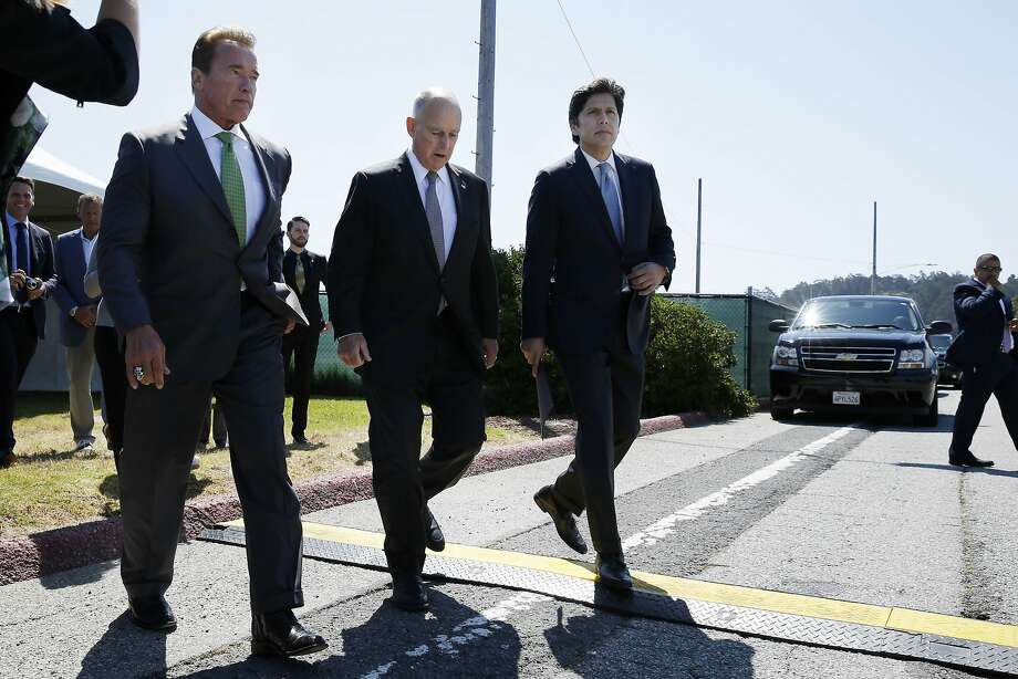 From front left: Former California Gov. Arnold Schwarzenegger, Gov. Jerry Brown and Senate President pro Tempore Kevin de León head to the signing ceremony at Treasure Island on Tuesday. Brown signed AB 398, a bill extending California's cap-and-trade system. Photo: Santiago Mejia, The Chronicle