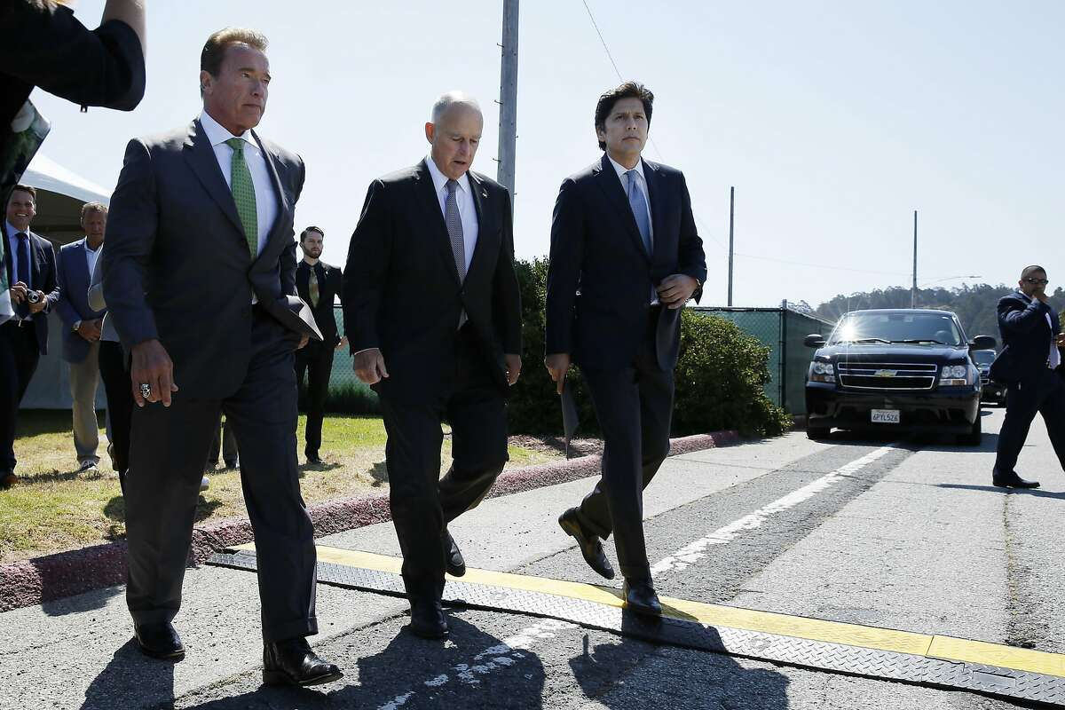 From front left: Former California Gov. Arnold Schwarzenegger, Gov. Jerry Brown and Senate President pro Tempore Kevin de León head to the signing ceremony at Treasure Island on Tuesday. Brown signed AB 398, a bill extending California's cap-and-trade system.