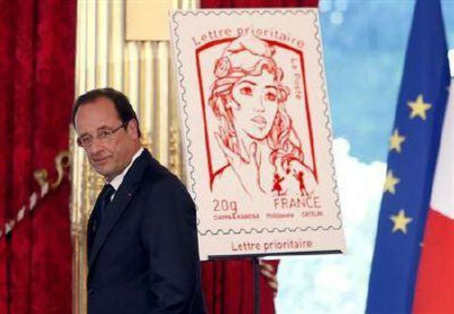 French President Francois Hollande unveils the new official Marianne post stamp at the Elysee Palace during the Bastille Day celebrations in Paris, July 14, 2013. (Reuters)