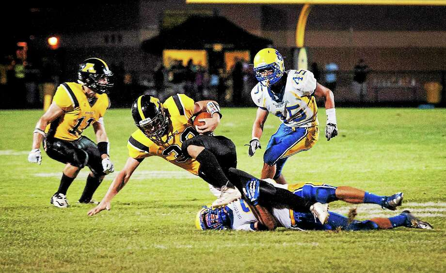 (Melanie Stengel — New Haven Register ) Amity's David Buono is brought down midfield in 2nd half action. Photo: Journal Register Co.