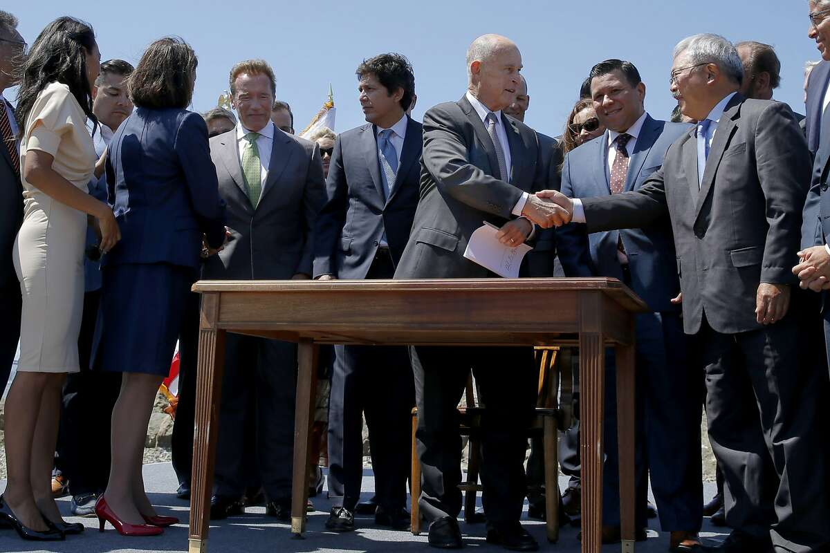 Gov. Jerry Brown and Mayor Ed Lee shake hands following a signing ceremony at Treasure Island on Tuesday, July 25, 2017, in San Francisco, Calif. Gov. Jerry Brown signed AB 398, a bill extending California's cap-and-trade system. He signed it on the same spot where former California Gov. Arnold Schwarzenegger signed the state's landmark 2006 climate change law, AB 32, which led to the creation of the cap-and-trade system.