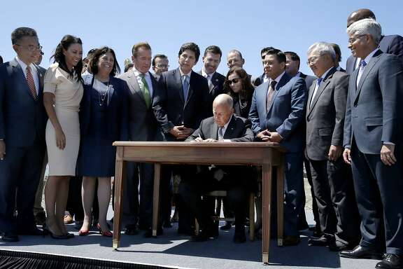 Gov. Jerry Brown signs AB 398 at Treasure Island on Tuesday, July 25, 2017, in San Francisco, Calif. AB 398 extends California's cap-and-trade system. Gov. Brown signed it on the same spot where former California Gov. Arnold Schwarzenegger signed the state's landmark 2006 climate change law, AB 32, which led to the creation of the cap-and-trade system.