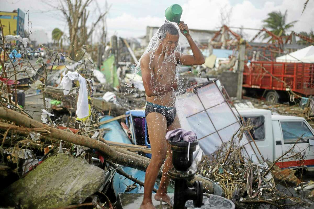 A man takes a shower amid rubble in an area badly affected by Typhoon Haiyan in Tacloban, central Philippines, Wednesday, Nov. 13, 2013. Typhoon Haiyan, one of the strongest storms on record, slammed into six central Philippine islands on Friday, leaving a wide swath of destruction. (AP Photo/Dita Alangkara)