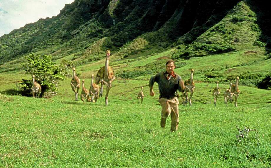 "FILE - In this 1993 file image originally released by Universal Pictures, Sam Neill, portraying Dr. Alan Grant, runs from dinosaurs in a scene from ""Jurassic Park."" The fourth installment of ""Jurassic Park"" has a name: ""Jurassic World."" Universal Pictures announced on Tuesday, Sept. 10, 2013, the film's new title and release date for the sequel to hatch in 3D on June 12, 2015. (AP Photo/Universal Pictures, File) Photo: AP / Universal Pictures"