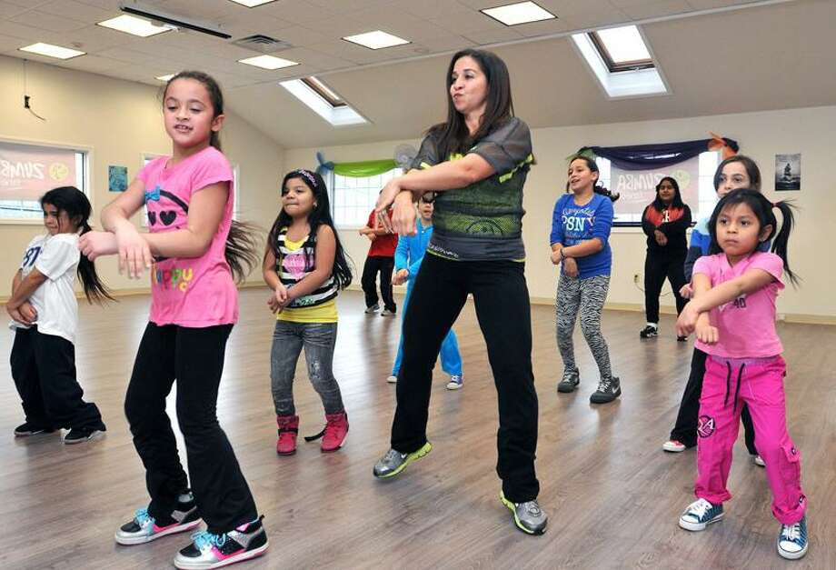 """West Haven--Emily Torres (left), 8, and Elini Kyriakides (right), 5, along with owner Ivette Altieri do the """"Gagnam Style"""" dance during a Zumba class at Viva! Z Fitness and Wellness studio. Torres is from West Haven and Kyriakides is from Woodbridge. Photo-Peter Casolino/Register <a href=""""mailto:pcasolino@newhavenregister.com"""">pcasolino@newhavenregister.com</a>"""