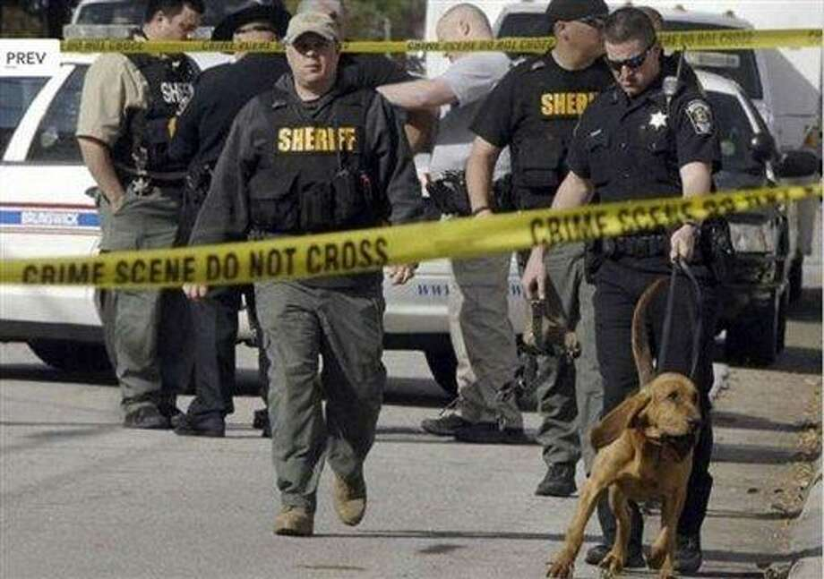 Authorities investigate the scene of shooting in Brunswick, Ga. on Thursday, March 21, 2013. A young boy opened fire on a woman pushing her baby in a stroller in a Georgia neighborhood, killing the 1-year-old boy and wounding the mother, police said. The woman, Sherry West, told WAWS-TV that two boys approached her and demanded money Thursday morning. Brunswick Police Chief Tobe Green said the boys are thought to be between 10 and 15 years old.(AP Photo/The Morning News, Terry Dickson) Photo: AP / The Morning News