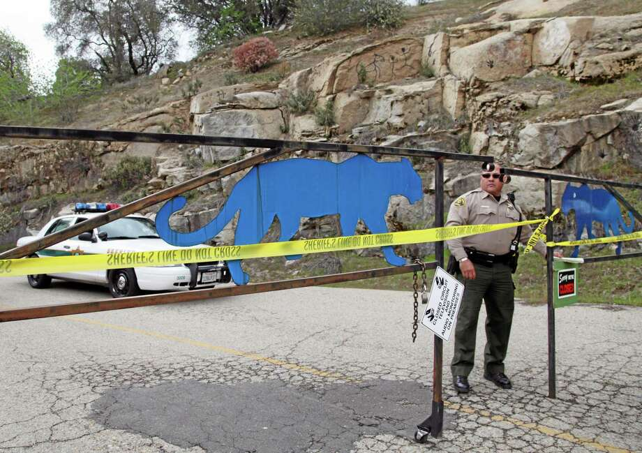 FILE - In this March 6, 2013 file photo, an officer guards the gate near at the entrance of Cat Haven, the exotic animal park in central California where a 26-year old female volunteer intern was killed by a lion, in Dunlap, Calif. Over the past few decades, as an exotic animal trade boomed and Americans bought up cute tiger and bear cubs, wild animal sanctuaries sprang up throughout the nation to take care of those wild animals once they grew to adult-size and were abandoned. Some of these sanctuaries focused on rescuing big wild cats. In turn, the growth in the trade of exotic animals and the number of sanctuaries that rescued them led to more humans handling predatory species and fueled an increase in wild cat-related incidents. (AP Photo/Gosia Wozniacka, File) Photo: AP / AP