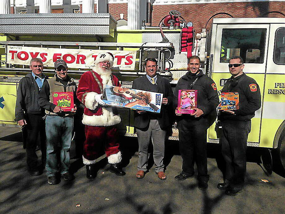 Santa, aka James Bartow of Milford, arrived Thursday at Milford City Hall to launch the 8th annual Milford Professional Firefighters Toys for Tots collection. Joining him, from left, are fire Lt. Brian Colwell, Lt. Jason Hall, Mayor Benjamin G. Blake, Firefighter Matt Ramos and Firefighter Phil Ragusa. Photo: Journal Register Co.