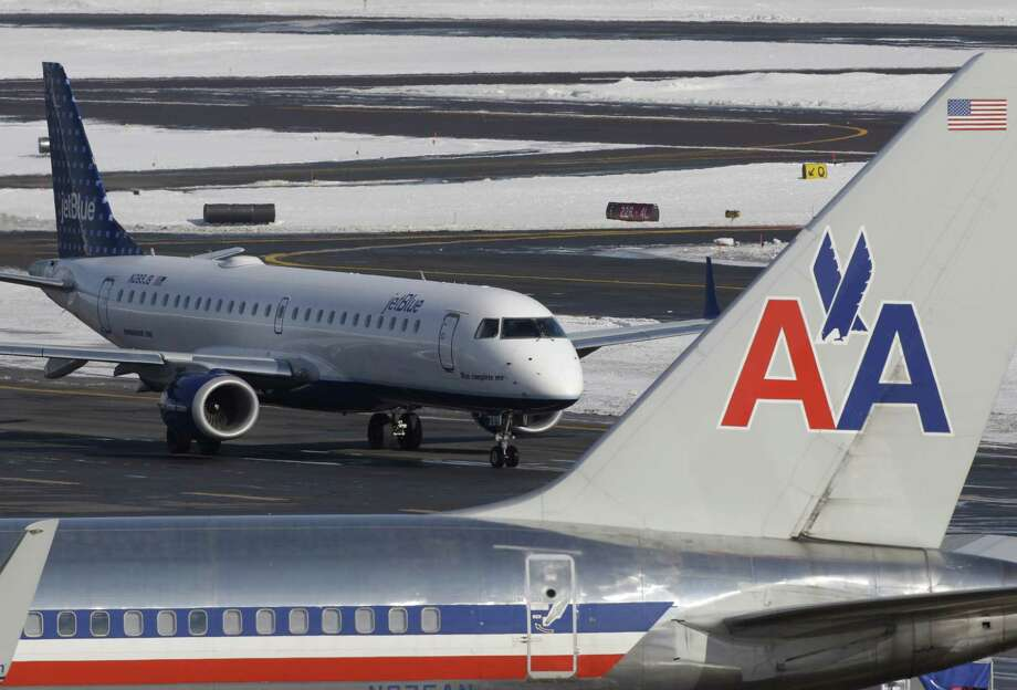 In this Thursday, Jan. 20, 2011 photo a Jet Blue jet taxis near an American Airlines jet parked at its gate at Boston's Logan International Airport. (AP Photo/Stephan Savoia) (Stephan Savoia) / AP