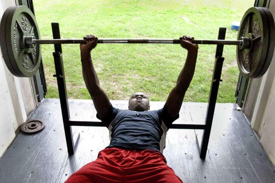 Melanie Stengel Register  West Haven High School football player, Ervin Philips, liftse weights during practice 7/15.