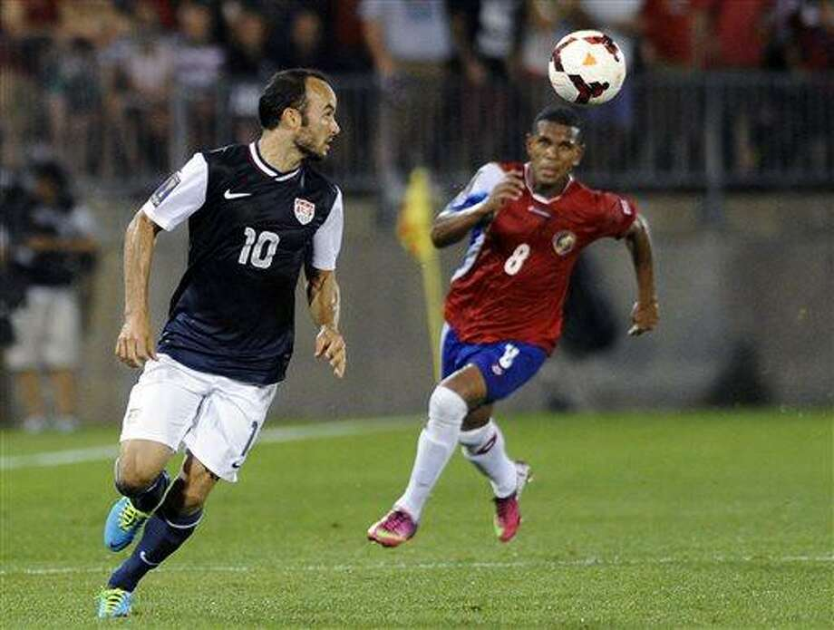 United States' Landon Donovan, left, sets up his game-winning assist while being watched by Costa Rica's Kenny Cunningham during the second half of a CONCACAF Gold Cup soccer match Tuesday, July 16, 2013, in East Hartford, Conn. Donovan passed to Brek Shea, who scored. The United States won 1-0. (AP Photo/Fred Beckham) Photo: AP / FR153656 AP