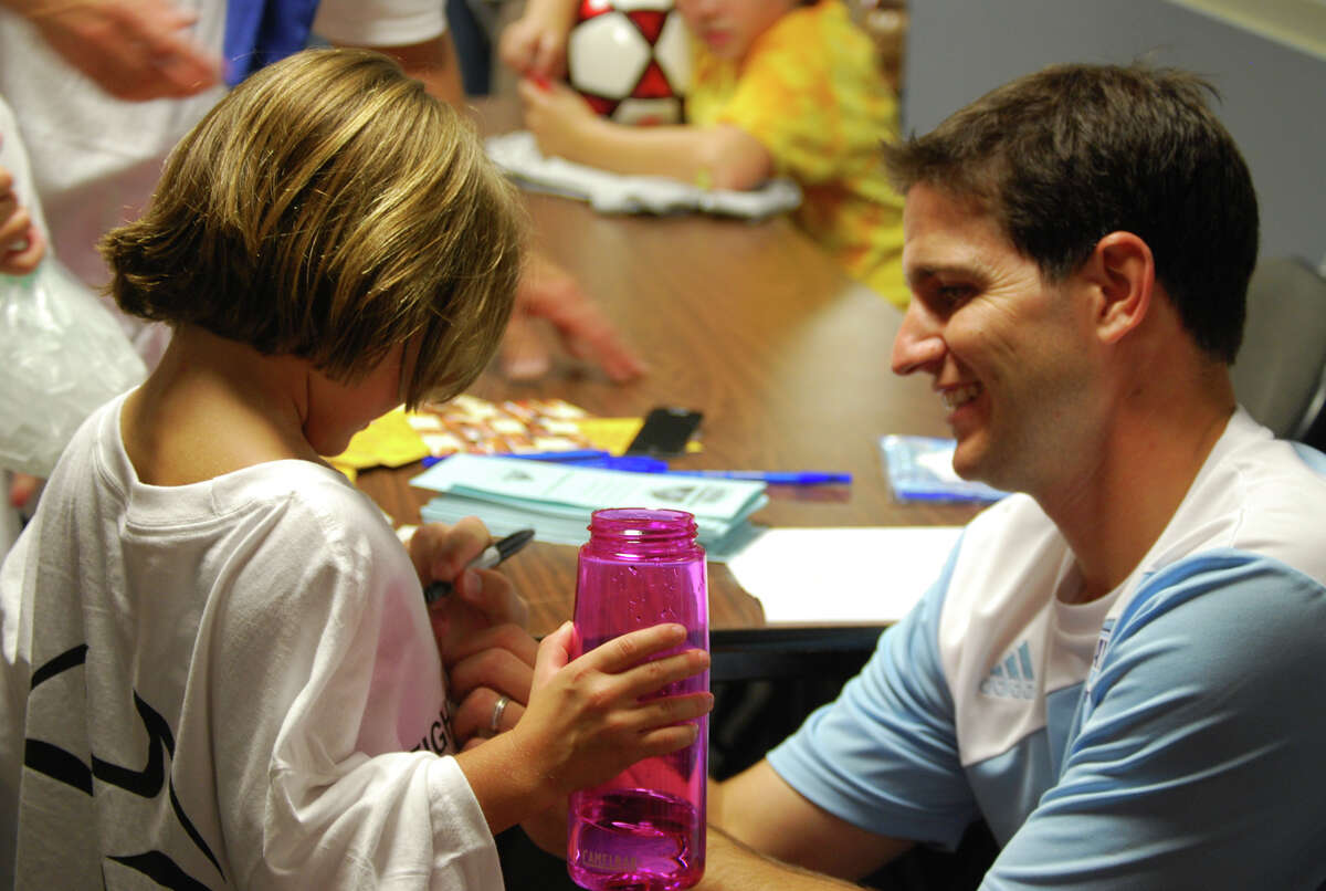 Miles Joseph of Clifton Park, former Major League Soccer player and US Olympian, signs an autograph for Michelle Osborn, 6, of Clifton Park, at a fundraiser Oct. 3 sponsored by Players Soccer Academy. The Capital District soccer community came together to support Nick Cammarata, 13, a student at Gowana Middle School in Clifton Park, who was recently diagnosed with leukemia. More than $3,500 was raised for the family through soccer clinics and t-shirt sales. The Sportsplex of Halfmoon donated its facility and Soccer Unlimited of Clifton Park donated t-shirts for the cause. To assist Cammarata, who needs a bone marrow transplate, go to http://www.caringbridge.org/visit/nickhealed. Marcie Van Epps photo.