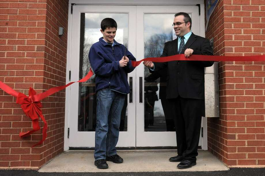 Harwinton Eagle Scout Adam Hall cuts the ribbon for the town' food pantry, which he helped construct, with First Selectman  Michael Criss.