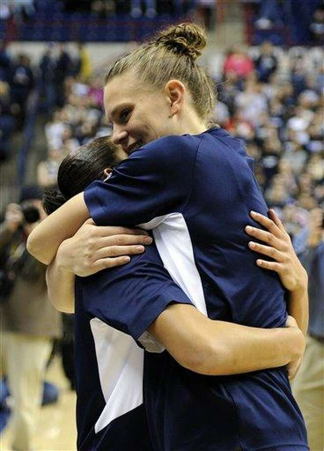Heather Buck, right, hugs Bria Hartley during Senior Night ceremonies before Connecticut's NCAA basketball game against Seton Hall in Storrs, Conn., Saturday, Feb. 23, 2013. (AP Photo/Fred Beckham) Photo: ASSOCIATED PRESS / AP2013