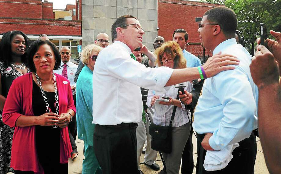 (Photo by Peter Hvizdak — Register)Governor Dannel P. Malloy, center, in New Haven to show his support for Toni Harp, left , in the New Haven democratic mayoral primary, answers questions posed to him by opposing democratic mayoral candidate Kermit Carolina, right,  at Lincoln-Bassett School in New HavenTuesday, September 10, 2013. Photo: New Haven Register / ©Peter Hvizdak /  New Haven Register