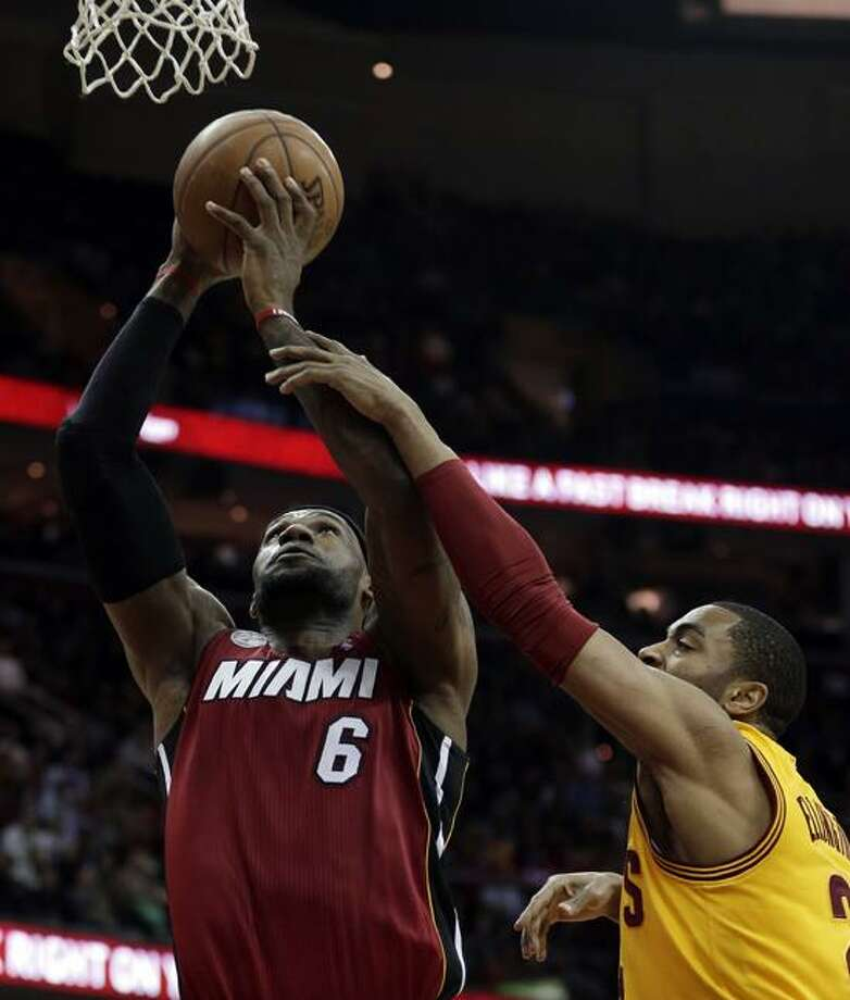 Cleveland Cavaliers' Wayne Ellington (21) fouls Miami Heat's LeBron James (6) during the first quarter of an NBA basketball game Wednesday, March 20, 2013, in Cleveland. (AP Photo/Tony Dejak) Photo: AP / AP2013