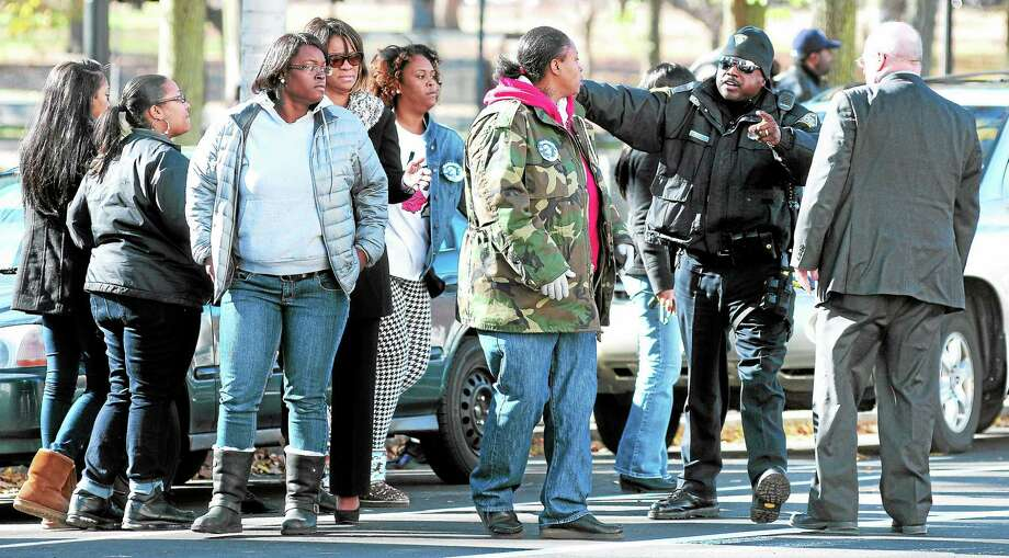 New Haven police keep the families of Erika Robinson and Adrian Bennett separated outside Superior Court in New Haven after the arraignment of Bennett in the shooting death of Robinson at the Key Club Cabaret. Photo: Arnold Gold — New Haven Register