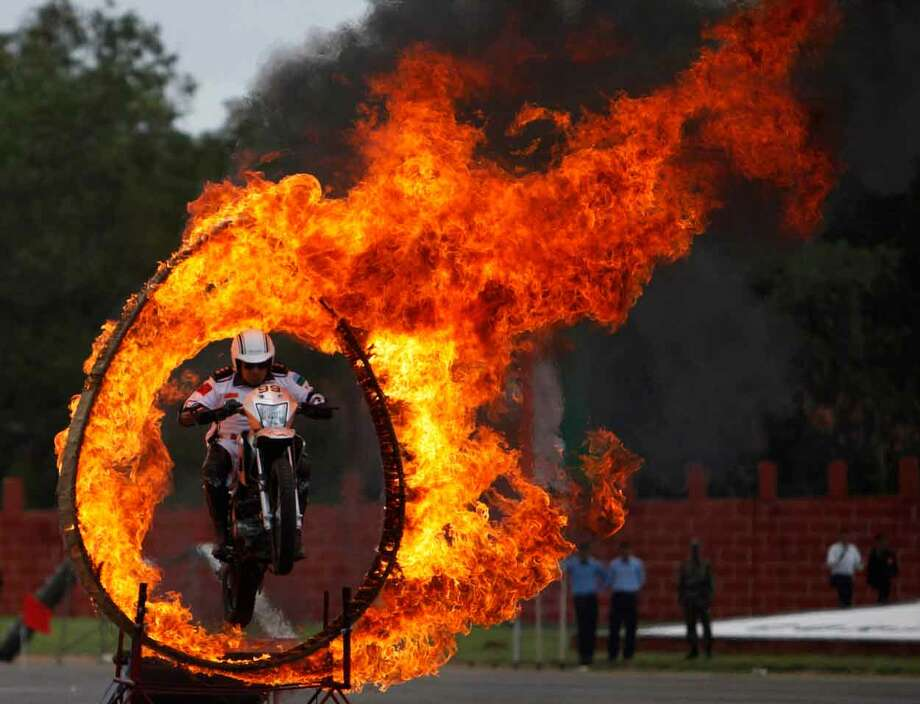 An Indian army soldier on a motorcycle performs a stunt during a display held as part of the sixtieth anniversary celebrations of the Military College of Electronics and Engineering in Hyderabad, India, Sunday, July 14, 2013. (AP Photo/Mahesh Kumar A.) Photo: ASSOCIATED PRESS / AP2013