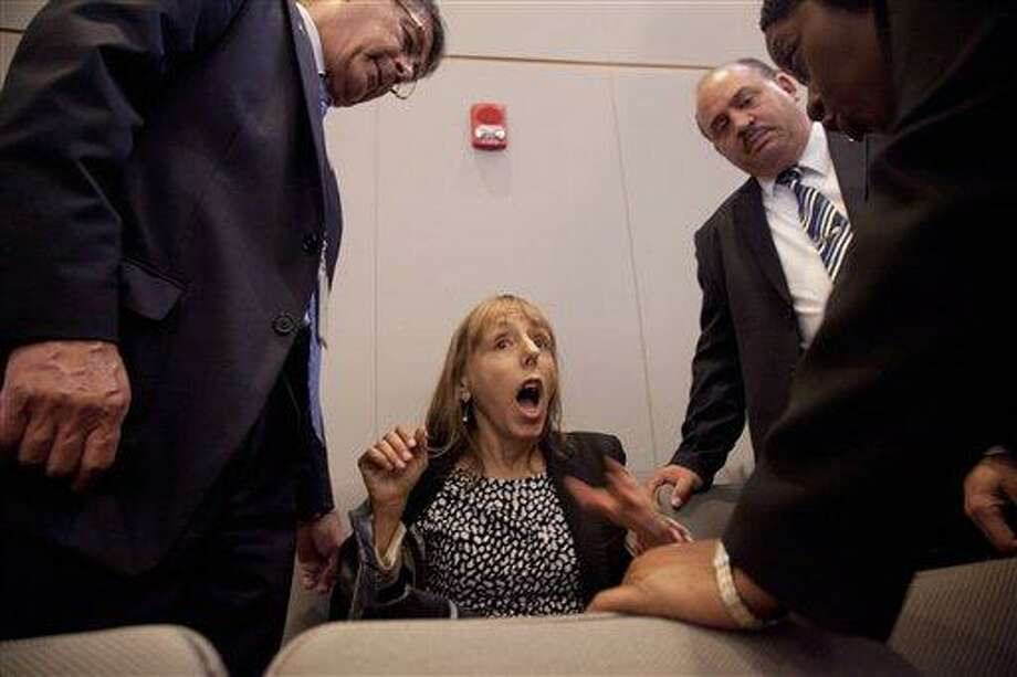 CODEPINK founder Medea Benjamin is surrounded by security as she shouts at President Barack Obama during his speech on national security, Thursday, May 23, 2013, at the National Defense University at Fort McNair in Washington. She was removed from the auditorium.  (AP Photo/Carolyn Kaster) Photo: AP / AP