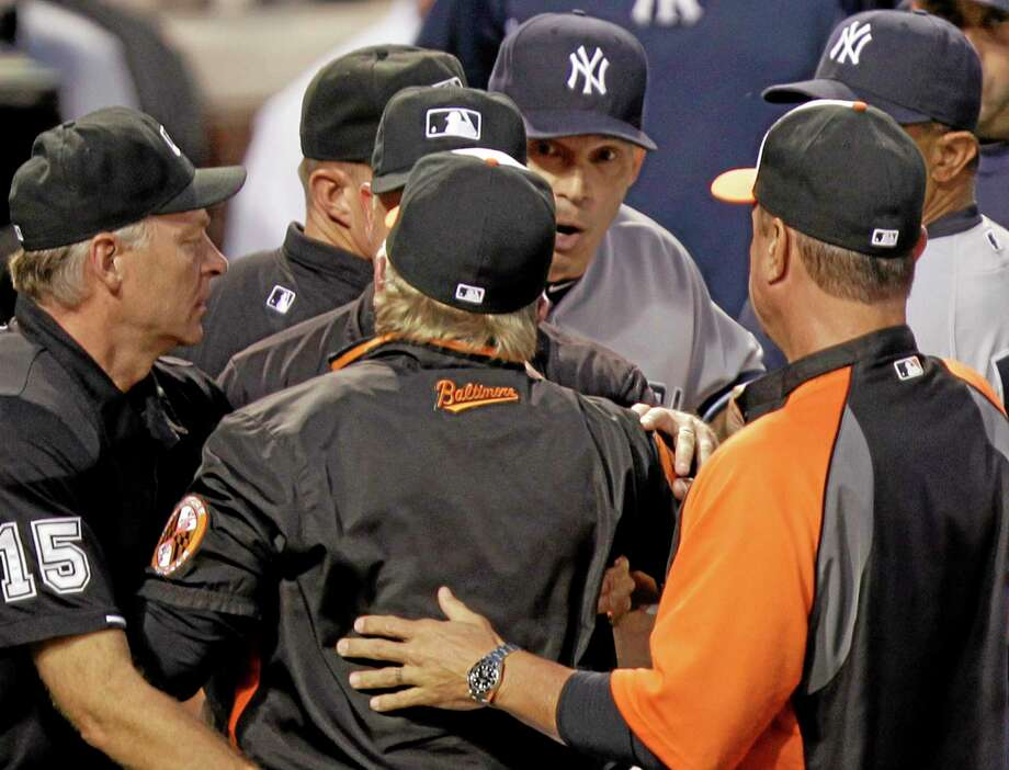 Orioles manager Buck Showalter, center back to camera, argues with Yankees manager Joe Girardi, center right, at the end of the first inning Monday. Photo: Luis M. Alvarez — The Associated Press   / FR596 AP