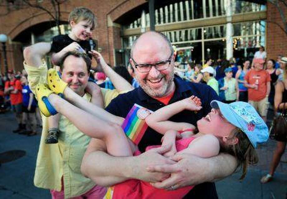 "Kyle Hanson, of Minneapolis, right, dances with his daughter Sofie, 6, as his husband John Stumme, of Minneapolis, dances with their son Henry, 3, during a party celebrating the signing of Minnesota's same-sex marriage biil at Ecolab Plaza in St. Paul, Minn. on Tuesday May 14, 2013. ""It's a huge day for our family,"" said Hanson, who was married to Stumme in California. ""We are finally equal with other families."" The couple plans to officially get married in Minnesota in August. Photo: ASSOCIATED PRESS / Ben Garvin2013"