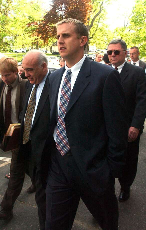 Former New Milford, Conn., police officer Scott Smith leaves Superior Court in Litchfield, Conn., Tuesday, May 20, 2003, after he opted for a second trial instead of a plea bargain offered him in connection with the December 1998 shooting death of Franklyn Reid. Smith's conviction on a manslaughter charge in Reid's death was overturned by the state Appellate Court. Next to Smith is his attorney, John Kelley.  (AP Photo/Bob Child) Photo: AP / AP