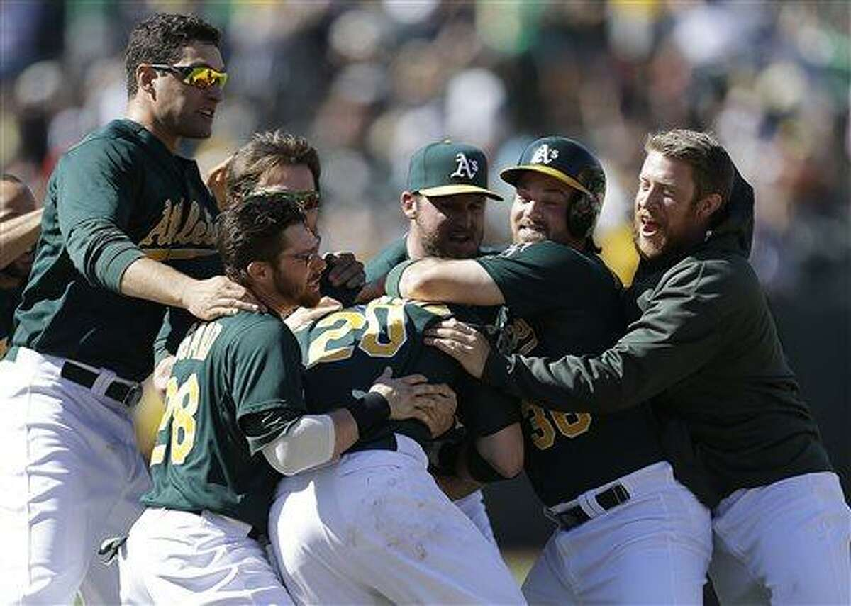 Oakland Athletics' Josh Donaldson (20) is mobbed by teammates after hitting the game-winning single in the 11th inning of a baseball game against the Boston Red Sox on Sunday, July 14, 2013, in Oakland, Calif. The A's won 3-2. (AP Photo/Ben Margot)