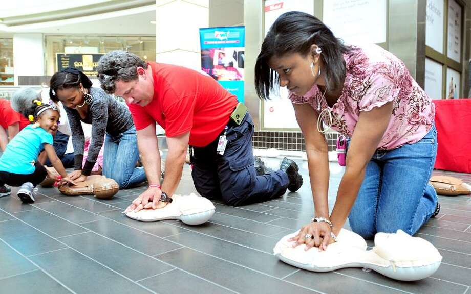 American Medical Response paramedic Steve Czenthe (center) teaches Keshawna Heard (left) of New Haven and Jasmine Hancock (right) of Branford how to perform chest compressions at the Westfield Connecticut Post Mall in Milford on 5/22/2013.  At far right is Heard's daughter, Samiya Bennett, 3.  Earlier in the day AMR personnel taught compression only CPR to over 3000 people at New Haven County schools.Photo by Arnold Gold/New Haven Register  AG0500A