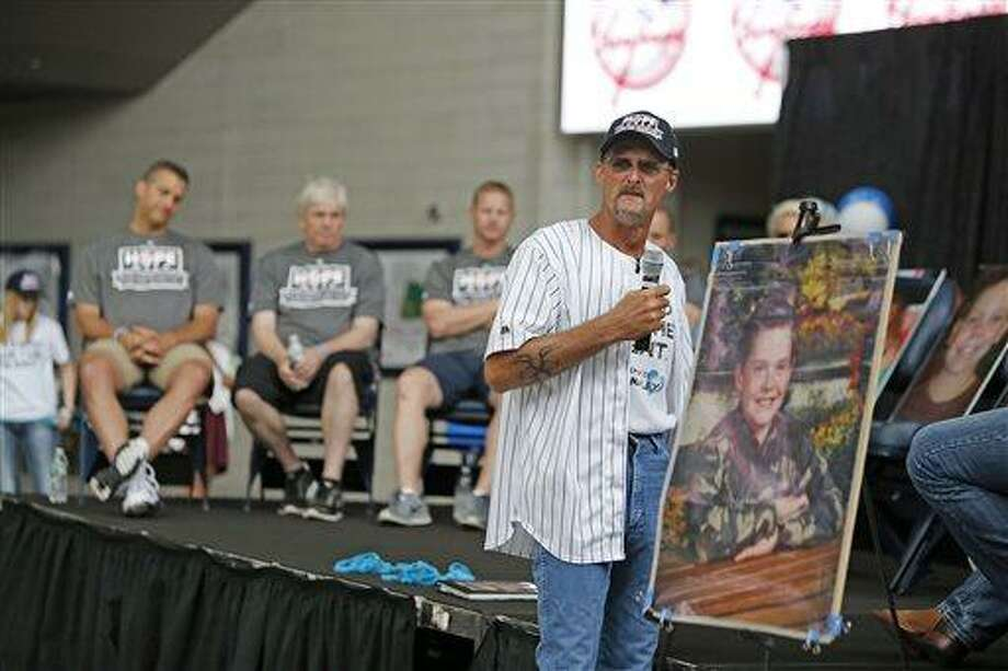 This photo provided by the New York Yankees, Krik Smalley holds a photo of his son during an anti-bullying presentation Friday, July 12, 2013, at Yankee Stadium in New York. A self-described private person thrust in front of a microphone by tragedy, Smalley ended up the face of the organization formed after his son Ty committed suicide May 13, 2010. (AP Photo/New York Yankees) Photo: AP / New York Yankees