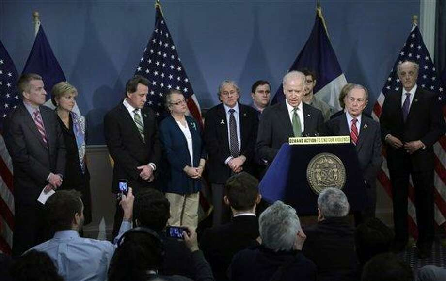 Chris and Lynn McDonnell, left, whose daughter Grace was killed in Newtown, Conn., and Neil Heslin, third left, whose son Jesse Lewis also died at the school shootings in Newtown, listen as Vice President Biden speaks in New York's City Hall Blue Room, Thursday, March 21, 2013. Relatives of shooting victims from Newtown, Conn., stood with New York Mayor Michael Bloomberg, foreground right, and Biden as they spoke in favor of an assault weapons ban. (AP Photo/Richard Drew) Photo: AP / AP