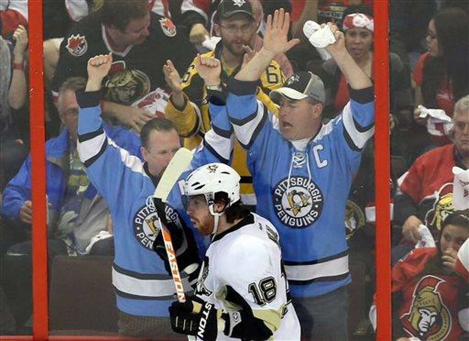 As fans, background, react, Pittsburgh Penguins' James Neal (18) celebrates his third-period goal against the Ottawa Senators during NHL playoff hockey playoff game action in Ottawa, Ontario, Wednesday, May 22, 2013. (AP Photo/The Canadian Press, Fred Chartrand) Photo: AP / The Canadian Press