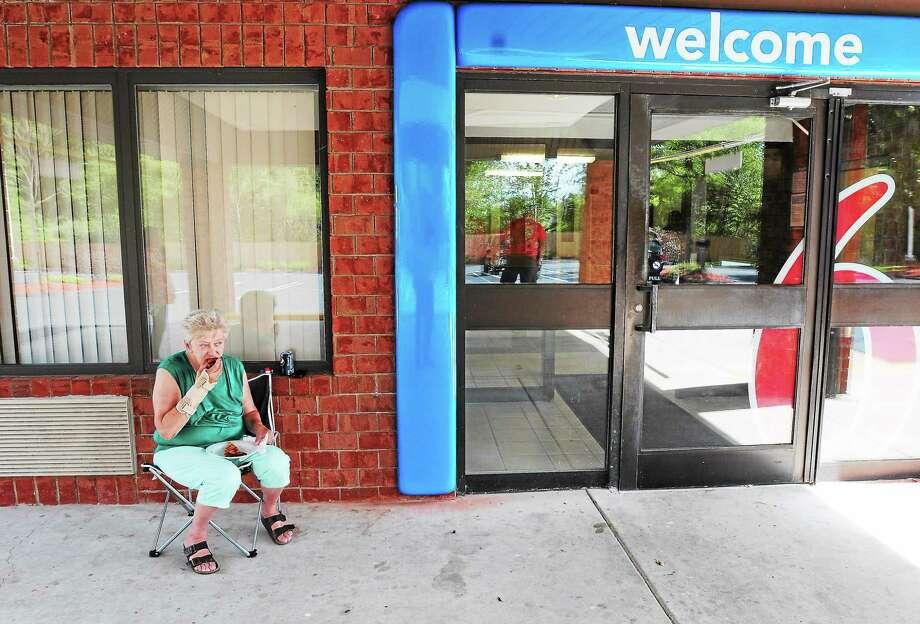 (Peter Hvizdak — Register)Lucille Remington, 67, a Bella Vista resident displaced by fire recently, eats pizza outside the Motel 6 in Branford Friday,September 6, 2013. Photo: New Haven Register / ©Peter Hvizdak /  New Haven Register