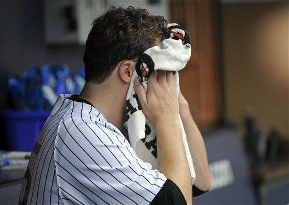 New York Yankees pitcher Phil Hughes towels off as he sits on the bench after being taken out of the baseball game during the eighth inning after he gave up a two-run home run to Minnesota Twins' Pedro Florimon Saturday, July 13, 2013, at Yankee Stadium in New York. (AP Photo/Bill Kostroun) Photo: AP / FR51951 AP