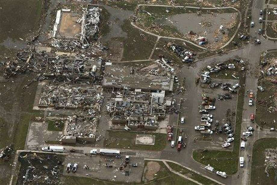 This aerial photo shows damage to buildings hit by a massive tornado in Moore, Okla., Monday May 20, 2013. A tornado roared through the Oklahoma City suburbs Monday, flattening entire neighborhoods, setting buildings on fire and landing a direct blow on an elementary school. (AP Photo/Steve Gooch) Photo: AP / AP