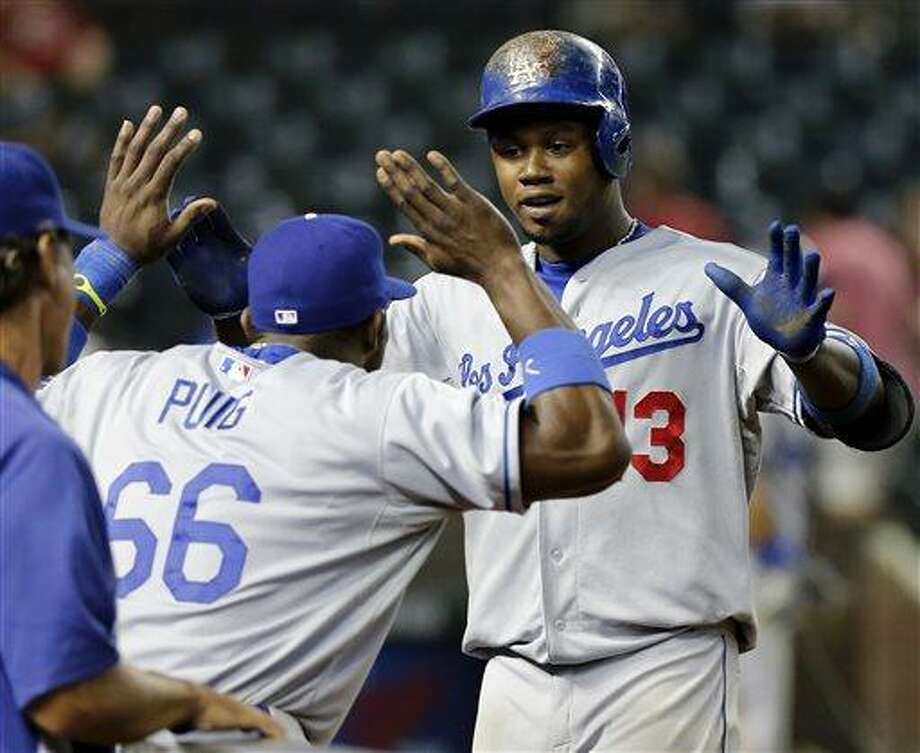 Los Angeles Dodgers Hanley Ramirez celebrates his solo home run against the Arizona Diamondbacks with teammate Yasiel Puig (66) during the14th inning of a baseball game, Wednesday, July 10, 2013, in Phoenix.  (AP Photo/Matt York) Photo: AP / AP