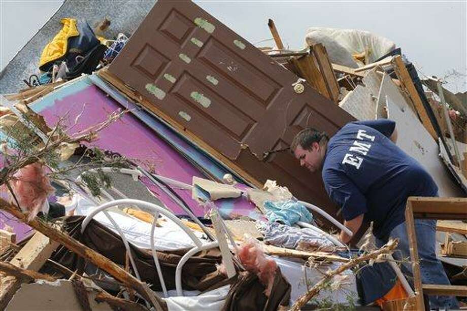 A resident who did not want to give his name, searches through the rubble of his mobile home in the Steelman Estates Mobile Home Park, destroyed by Sunday's tornado, near Shawnee, Okla., Monday, May 20, 2013. The tornado that slammed into Oklahoma on Sunday is now blamed for two deaths. Authorities say two men in their 70s have been found dead in or near a mobile home park outside of Shawnee. (AP Photo Sue Ogrocki) Photo: AP / AP