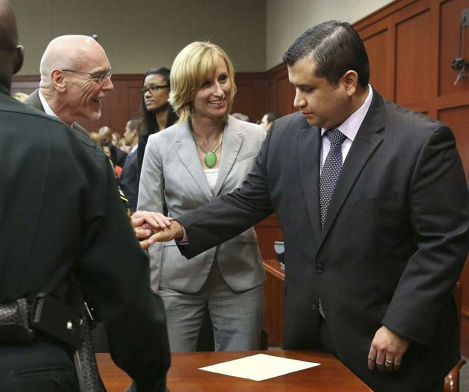 George Zimmerman, right, is congratulated by his defense team after being found not guilty during  Zimmerman's trial in Seminole Circuit Court in Sanford, Fla. on Saturday, July 13, 2013. Jurors found Zimmerman not guilty of second-degree murder in the fatal shooting of 17-year-old Trayvon Martin in Sanford, Fla. The six-member, all-woman jury deliberated for more than 15 hours over two days before reaching their decision Saturday night. (AP Photo/Gary W. Green, Pool) Photo: AP / Orlando Sentinel POOL