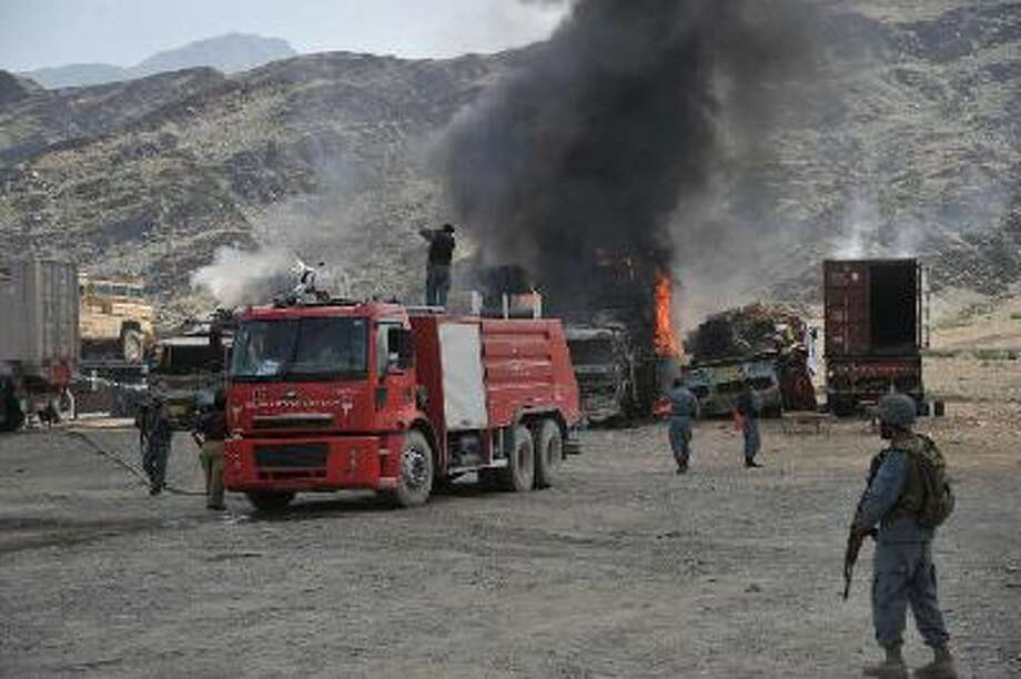 Afghan security personel stand alert near burnt military vehicles after a clash between Taliban and Afghan security forces in Torkham on September 2, 2013.