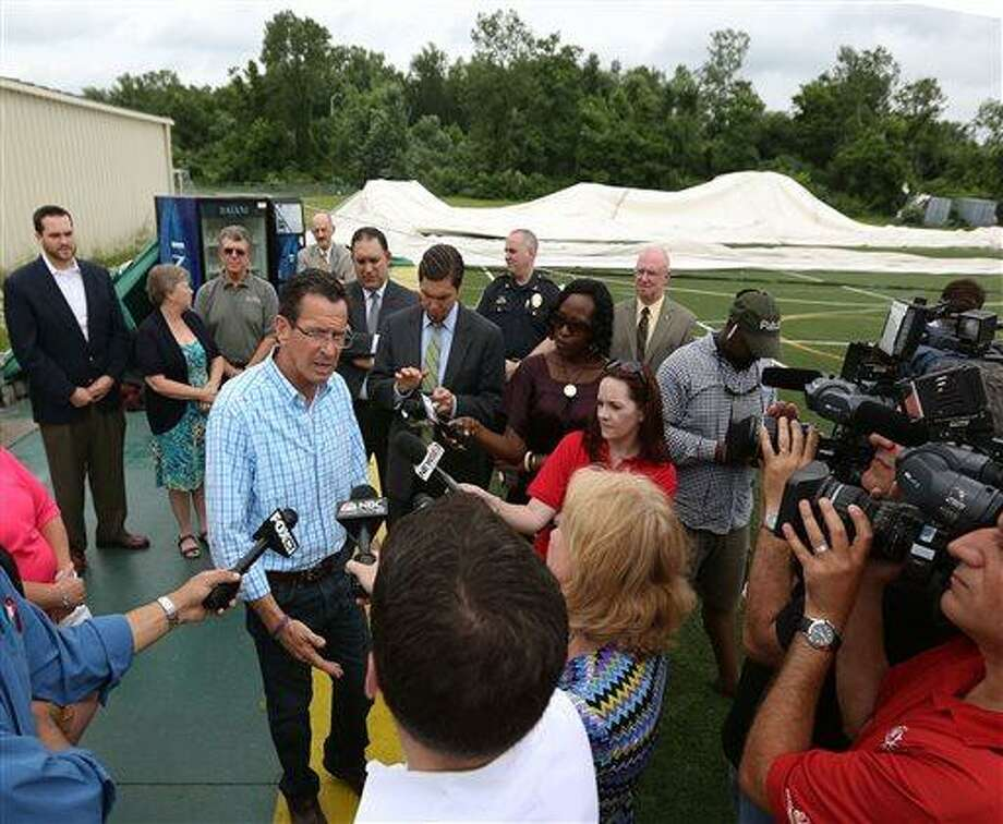 Connecticut Governor Dannel Malloy, left, addresses the media at Sports World in East Windsor Conn. on Tuesday, July 2, 2013. Gov. Malloy was touring the damage caused by Monday's EF01 tornado. 29 campers were in the domed bubble on Monday, but were safely clear of it and undercover before the tornado hit. The twister which formed in Windsor Conn. and spread a 2 1/2 mile long path of damage generated winds up to 86 miles per hour. (AP Photo/Journal Inquirer, Jared Ramsdell) Photo: AP / Journal Inquirer
