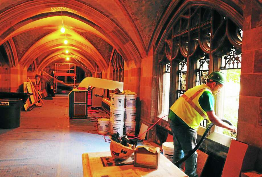 Kenneth Lambides, site foreman for Femendella & Associates of New Jersey, vacuums glazing debris in the north aisle of Yale University's Sterling Memorial Library after stained-glass windows were removed for reglazing Friday. Photo: (Peter Hvizdak — Register)   / ©Peter Hvizdak /  New Haven Register
