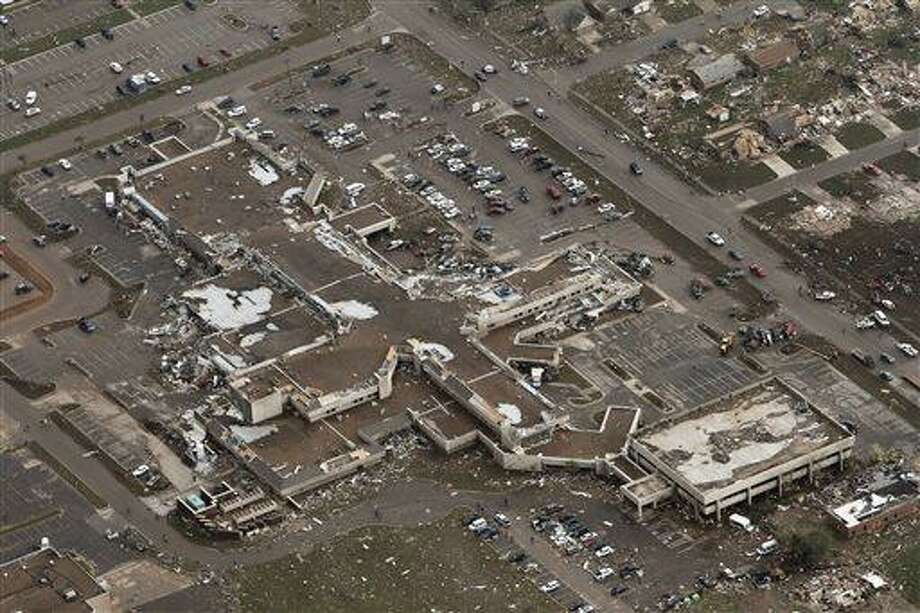 This aerial photo shows damage to Moore Medical Center after it was hit by a massive tornado in Moore, Okla., Monday May 20, 2013. A tornado roared through the Oklahoma City suburbs Monday, flattening entire neighborhoods, setting buildings on fire and landing a direct blow on an elementary school. (AP Photo/Steve Gooch) Photo: ASSOCIATED PRESS / AP2013