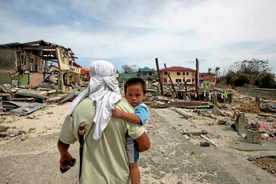 A man walks home with his son Monday Nov. 11, 2013, following Friday's devastating typhoon that lashed Hernani township, in eastern Samar province, in the central Philippines. Typhoon-ravaged Philippine islands faced an unimaginably huge recovery effort that had barely begun Monday, as bodies lay uncollected and uncounted in the streets and survivors pleaded for food, water and medicine. (AP Photo/Bullit Marquez) Photo: AP / AP