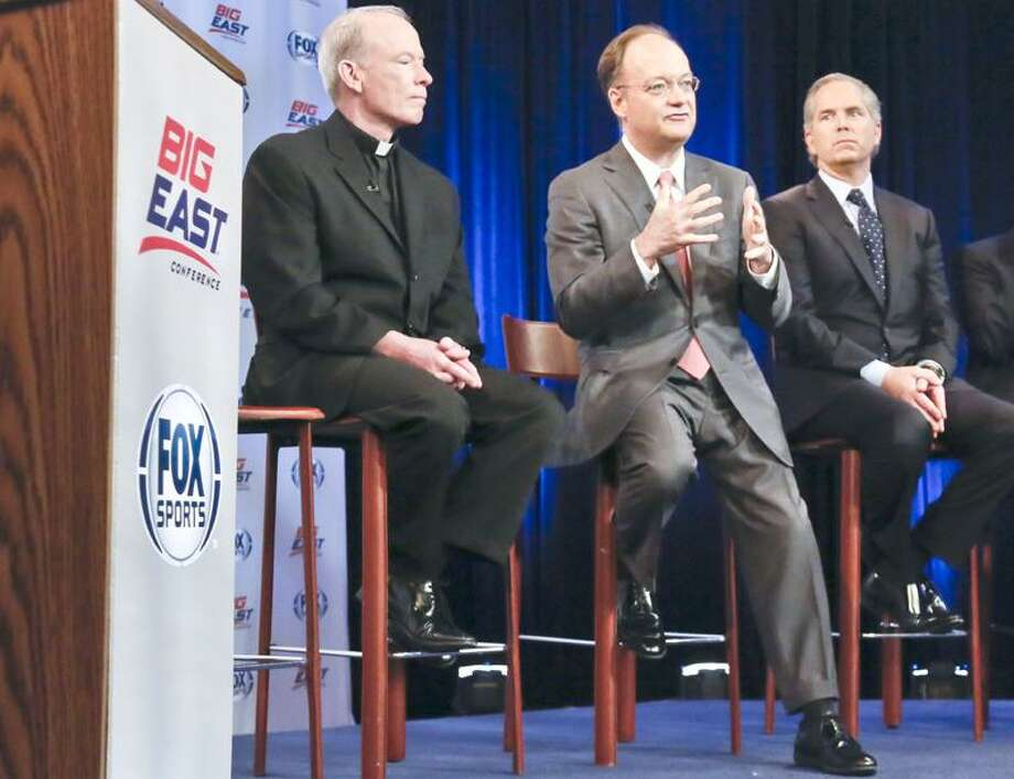 Providence President Rev. Brian Shanley, left, Georgetown President John DeGioia, center, and FOX Sports President and COO Randy Freer, right, appear during a news conference on Wednesday, March 20, 2013 in New York. Big East Conference schools gathered in New York to announce developments helping to shape the new NCAA college basketball focused conference. (AP Photo/Bebeto Matthews) Photo: AP / AP