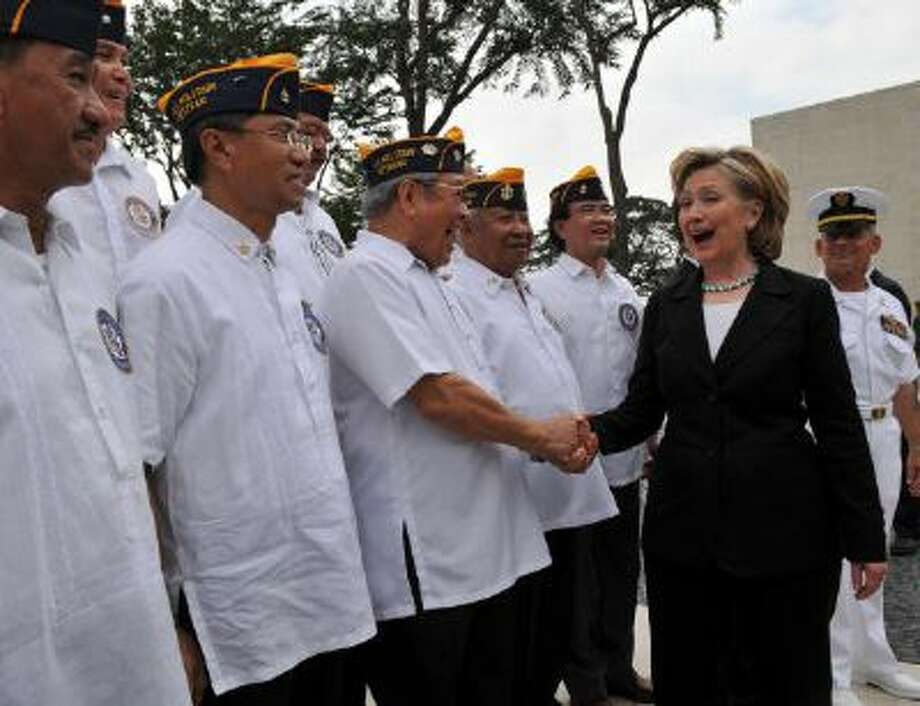 US Secretary of State Hillary Clinton (R) smiles as she is greeted by Filipino-American military veterans during the wreath laying ceremony at the Manila American cemetery in Manila on November 13, 2009. Clinton said the time was ripe for the Philippines to finally seal a peace deal with the country's largest Muslim separatist group and end a 30-year insurgency. AFP PHOTO/TED ALJIBE (Photo credit should read TED ALJIBE/AFP/Getty Images) Photo: AFP/Getty Images / 2009 AFP
