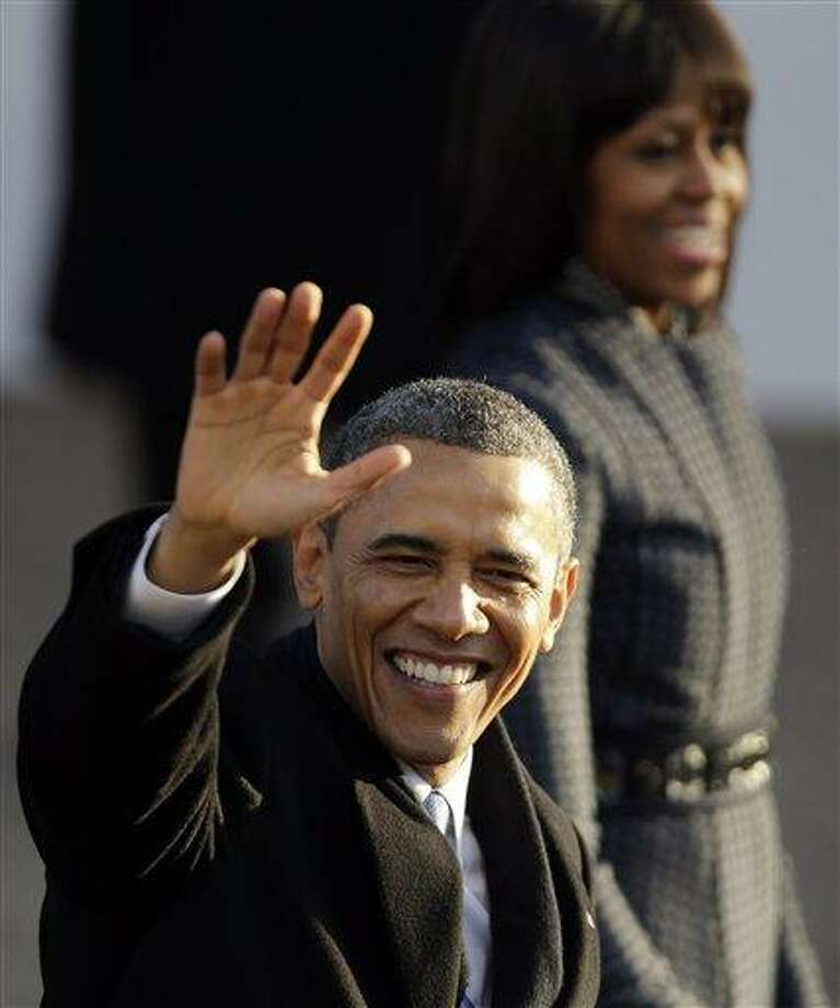 President Barack Obama and first lady Michelle Obama walk the inaugural parade route walk down Pennsylvania Avenue en route to the White House, Monday, Jan. 21, 2013, in Washington. Thousands  marched during the 57th Presidential Inauguration parade after the ceremonial swearing-in of President Barack Obama. (AP Photo/Gerald Herbert) Photo: AP / AP