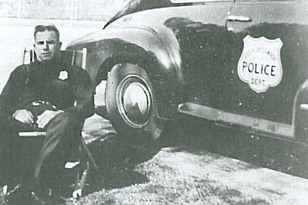 Conroe's first Chief of Police Eddie Stephan with Conroe's first police car. It was a 1947 Oldsmobile bought for about $1,000.