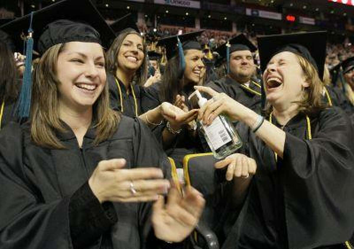 Graduates pass a bottle of hand sanitizer to other graduates at the start of Northeastern University's commencement ceremony in Boston Friday, May 1, 2009. (AP Photo/Elise Amendola)