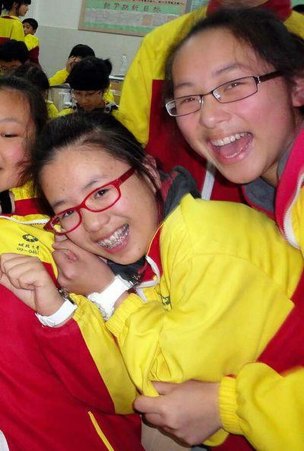 In this undated photo made available Monday, July 8, 2013, Ye Mengyuan, left, and Wang Linjia, right, pose for photos with other classmates in the classroom in Jiangshan city in eastern China's Zhejiang province. Chinese state media and Asiana Airlines have identified the two victims of the Asiana Airlines crash at San Francisco International Airport. Photo: AP / CHINATOPIX net
