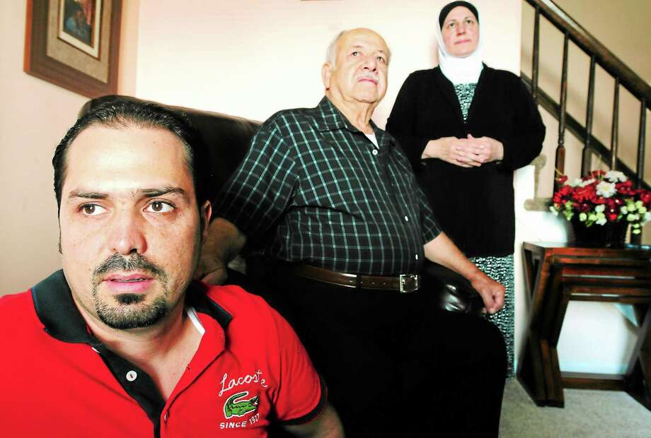 Talal Altrabulsi, 33, of Milford, left, is seen in his Milford home with his grandfather, Yousef Nahlawi, 80, and his aunt, Fatena Nahlawi, 56. Photo: Peter Hvizdak — Register   / ©Peter Hvizdak /  New Haven Register