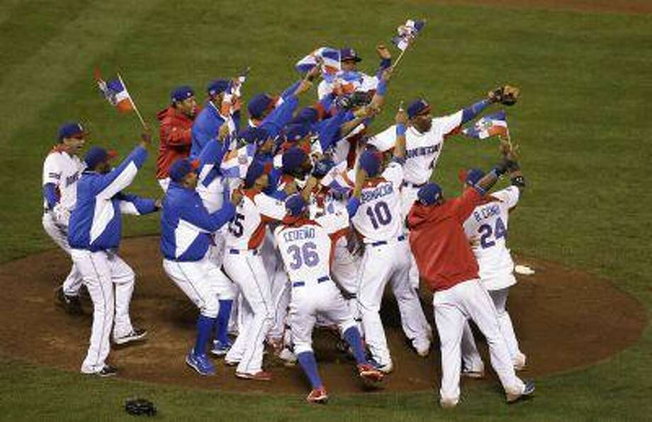 The Dominican Republic players celebrate after beating Puerto Rico in the championship game of the World Baseball Classic in San Francisco, Tuesday, March 19, 2013. The Dominican Republic won 3-0. (AP Photo/Jeff Chiu) Photo: AP / AP